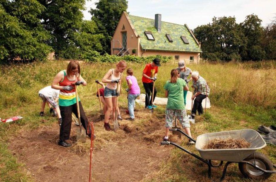 Das geht ganz schön in die Muskeln: Die Schüler der AG heben mit Spaten bewaffnet das Gras von dem Grabungsfeld ab - und stoßen auch hier schon auf ein paar Scherben