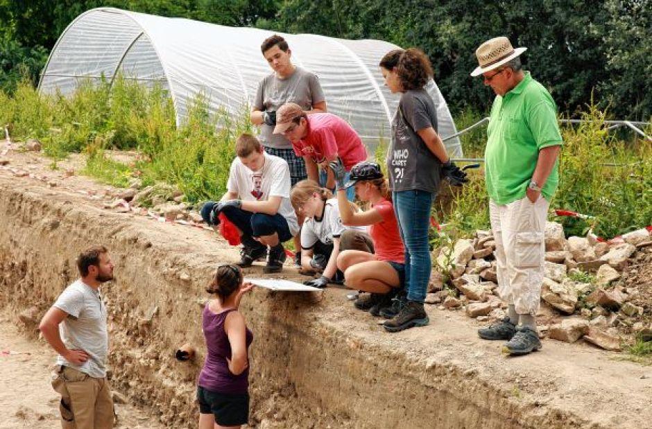 Grabungsleiter Justin Schmidt von der Uni Heidelberg (unten rechts, l.) zeigt den Schülern Skizzen des Burgverlaufs.